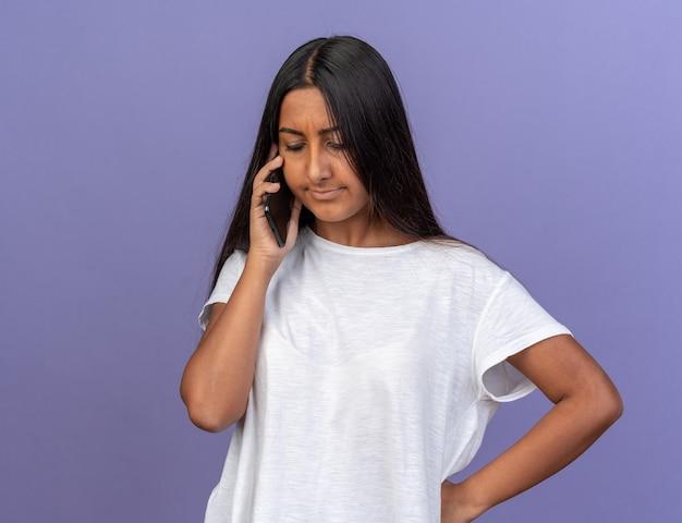 Menina com uma camiseta branca parecendo descontente enquanto fala no celular em pé sobre o azul