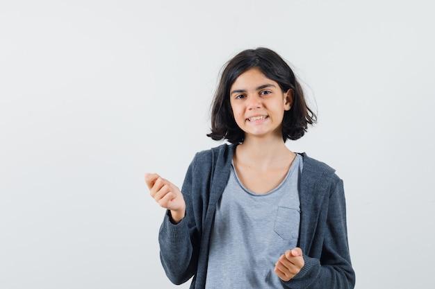 Menina com uma camiseta cinza claro e um capuz cinza escuro com zíper na frente e os punhos cerrados e parecendo fofa
