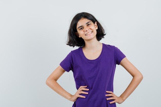 Menina com uma camiseta de mãos dadas na cintura e parecendo alegre,