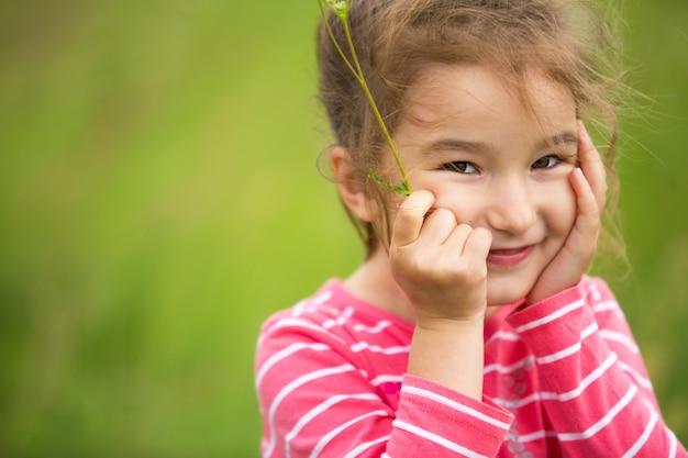 Menina com uma camiseta listrada coral sobre um fundo verde em um campo segura o rosto nas mãos e sorri maliciosamente. dia das crianças, criança feliz, proteção do meio ambiente e da natureza, repelente de insetos