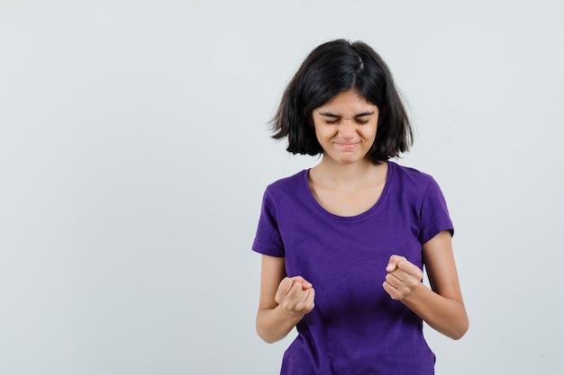 Menina com uma camiseta mostrando o gesto do vencedor e parecendo feliz,