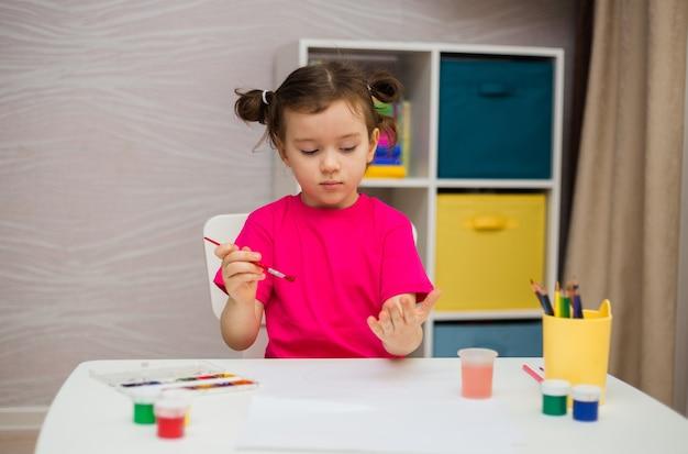 Menina com uma camiseta rosa se senta a uma mesa e desenha com um pincel e tintas