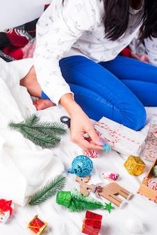 Menina com uma camisola de malha aconchegante, decorada com uma caixa de presente de natal