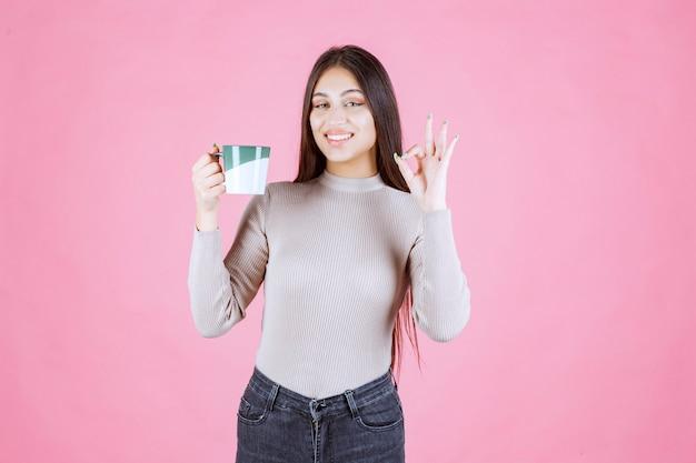 Menina com uma caneca de café fazendo sinal de satisfação