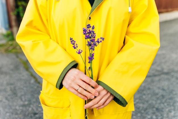 Menina com uma capa de chuva amarela segurando hastes de lavanda nas mãos