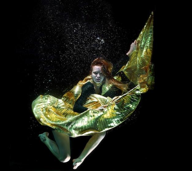 Menina com uma capa dourada sob a água