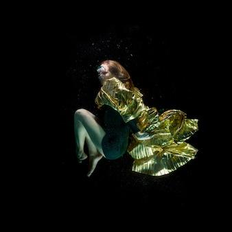 Menina com uma capa sob a água