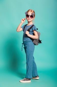 Menina com uma cauda em roupas elegantes e óculos escuros sobre fundo azul