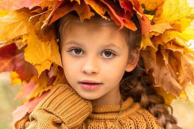Menina com uma coroa de outono de folhas de plátano.