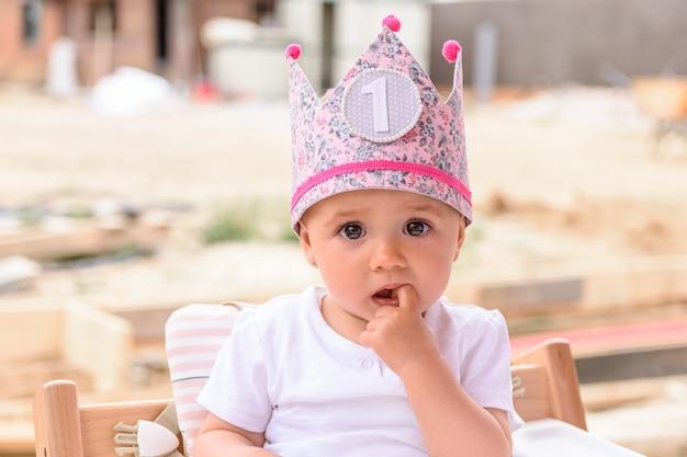 Menina com uma coroa rosa em seu primeiro aniversário
