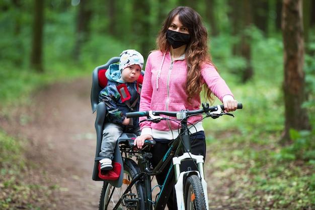Menina com uma criança andando de bicicleta em uma máscara médica no rosto