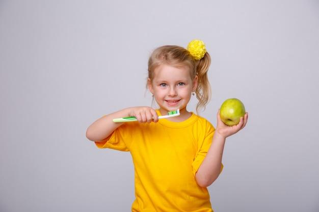 Menina com uma escova de dentes, menina com uma escova de dentes e uma maçã.