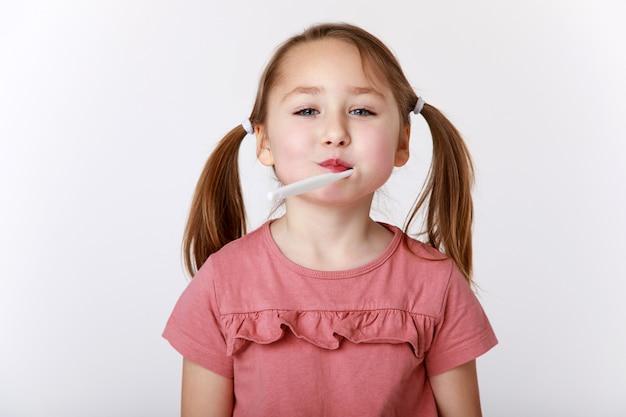 Menina com uma escova de dentes na boca