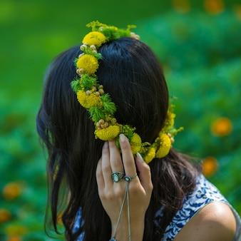 Menina com uma faixa principal de grinalda floral verde amarelo.