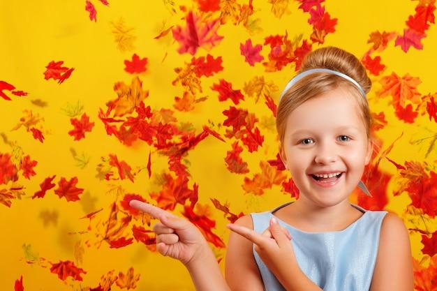 Menina com uma fantasia de princesa em um fundo de folhas de outono caindo