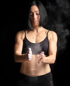 Menina com uma figura de esportes vestida com um top preto bate palmas nas mãos com magnésia branca