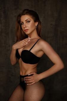 Menina com uma figura perfeita em lingerie preta e meia-calça em uma parede escura