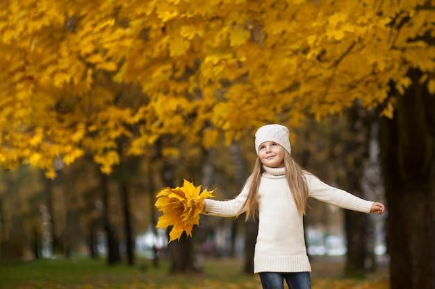 Menina com uma folha de plátano nas mãos dela. em um suéter leve e chapéu