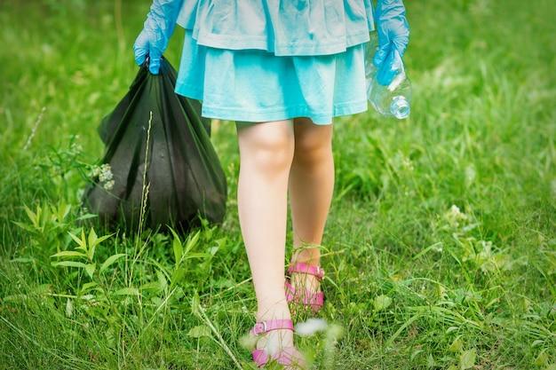 Menina com uma garrafa de plástico amassada e um saco de lixo nas mãos enquanto limpa o lixo no parque