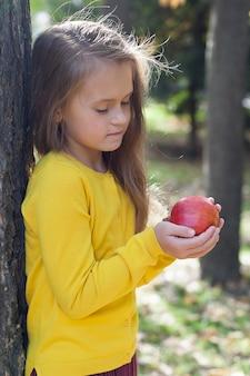 Menina com uma jaqueta amarela fica no parque e segura romãs maduras.