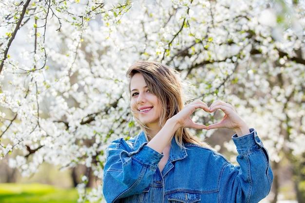 Menina com uma jaqueta jeans fica perto de uma árvore florida e mostra o sinal da mão do coração no parque. temporada de primavera