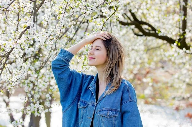 Menina com uma jaqueta jeans fica perto de uma árvore florida no parque. temporada de primavera