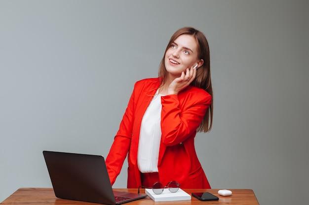 Menina com uma jaqueta vermelha falando ao telefone enquanto usa o laptop