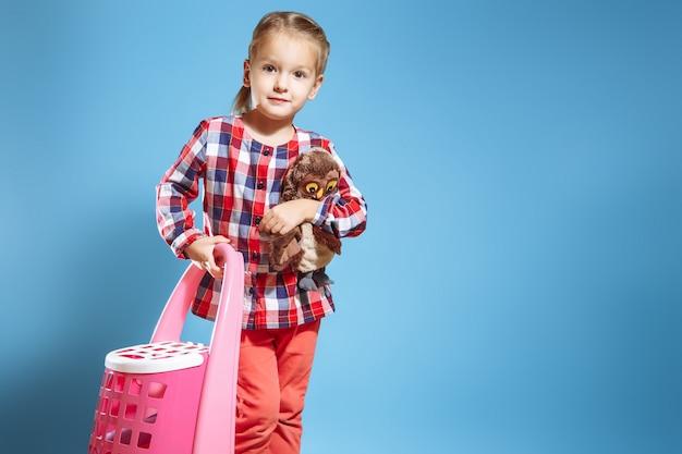 Menina com uma mala e um brinquedo favorito sobre um fundo azul. conceito de viagens