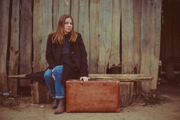 Menina com uma mala no banco contra o pano de fundo da cerca velha