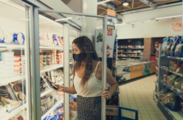 Menina com uma máscara abrindo uma geladeira no supermercado.
