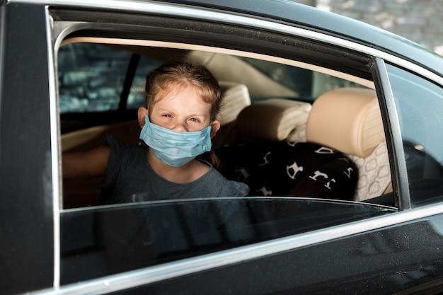 Menina com uma máscara médica está sentada em uma cadeira de criança no carro.