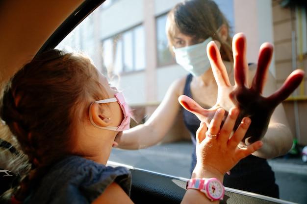 Menina com uma máscara médica está sentado em uma cadeira de criança no carro.