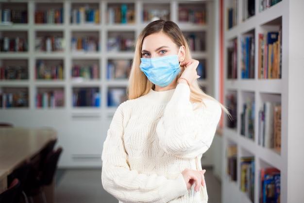 Menina com uma máscara protetora na biblioteca da universidade. conceito de infecção por coronavírus.
