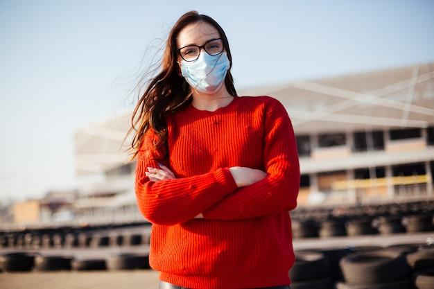 Menina com uma máscara, vestindo um suéter vermelho ao ar livre
