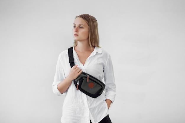 Menina com uma mochila de fanny na frente de uma parede branca