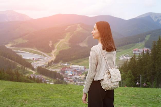 Menina com uma mochila de pé na colina e admirando as montanhas. cidade à distância