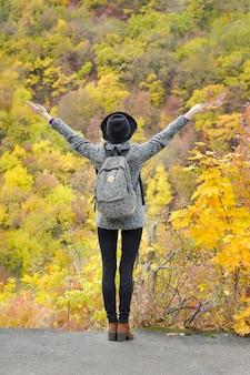 Menina com uma mochila e um chapéu em pé com os braços levantados