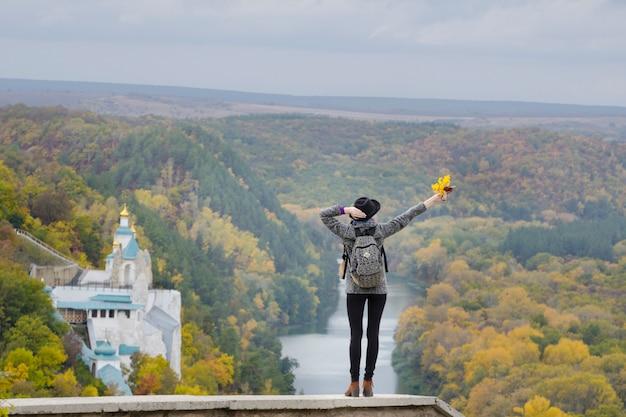 Menina com uma mochila e um chapéu em pé em uma colina. mãos levantadas. rio e templo abaixo.