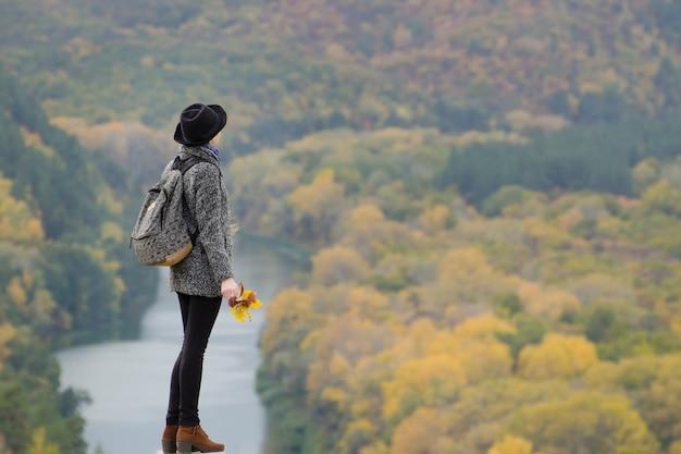 Menina com uma mochila e um chapéu em pé em uma colina