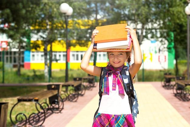Menina com uma mochila e uma pilha de livros na cabeça perto da escola. de volta à escola