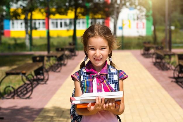 Menina com uma mochila e uma pilha de livros perto da escola. de volta às aulas, aluno feliz, livros pesados. educação, aulas do ensino fundamental, início do ano letivo, 1º de setembro