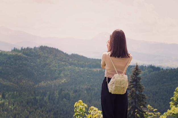 Menina com uma mochila em um smartphone fotografias de montanhas e florestas. vista traseira. dia ensolarado de verão