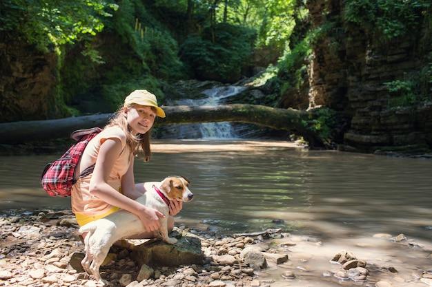 Menina com uma mochila em uma caminhada nas montanhas nas cachoeiras com o cachorro jack russel