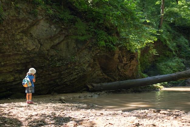 Menina com uma mochila em uma caminhada nas montanhas nas cachoeiras