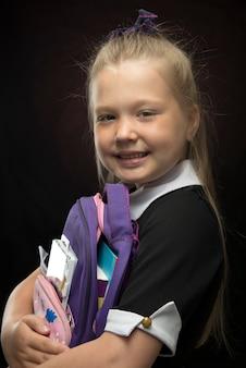 Menina com uma mochila escolar nas mãos em uma parede preta. volta às aulas e conceito de educação