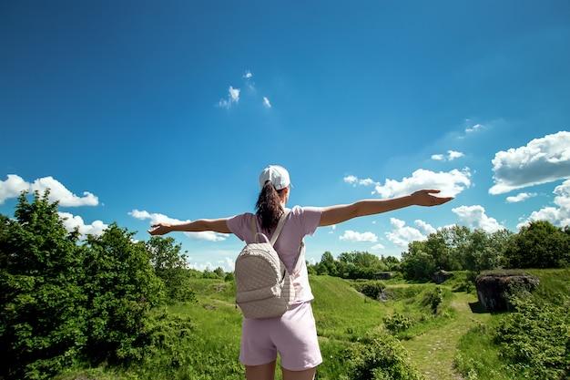 Menina com uma mochila no fundo de uma bela paisagem.