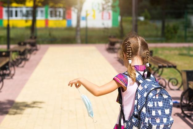 Menina com uma mochila perto da escola depois das aulas com a máscara médica removida