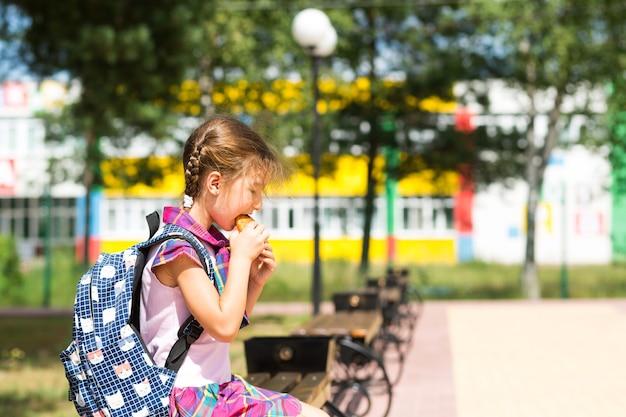 Menina com uma mochila, sentado em um banco e comendo uma torta perto da escola. um lanche rápido com pão, comida não saudável, almoço em casa. de volta à escola. educação, aulas do ensino fundamental, 1º de setembro