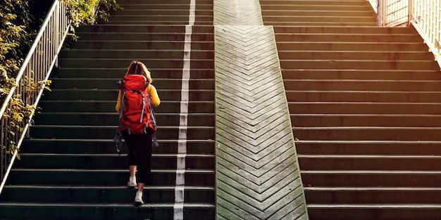 Menina com uma mochila subindo as escadas