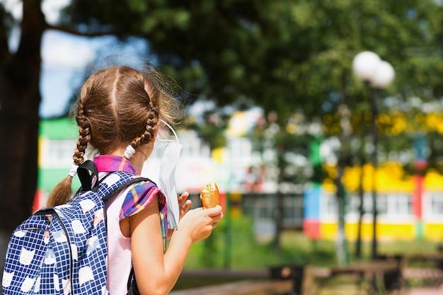 Menina com uma mochila tira a máscara médica e comendo torta perto da escola. um lanche rápido com pão, comida não saudável, almoço em casa. de volta à escola. educação, aulas do ensino fundamental, 1º de setembro